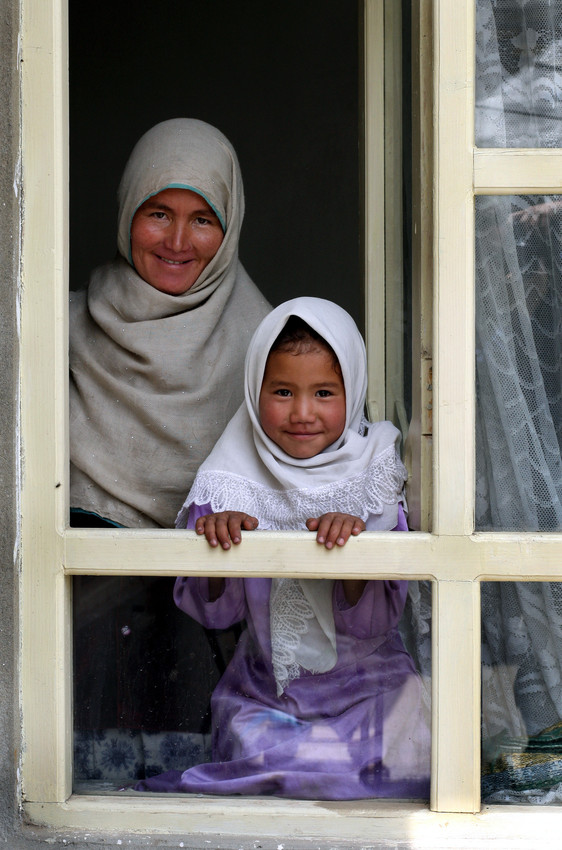 Women Key to Ending Global Poverty -  A muslim woman and child look out a window in Afghanistan.