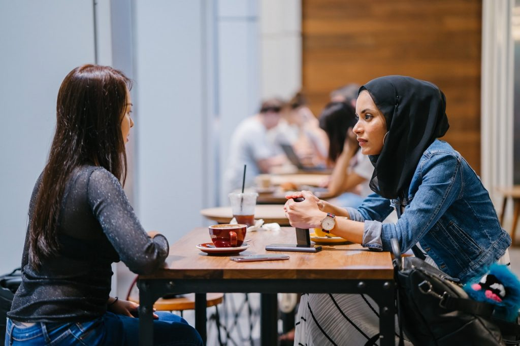 Muslim woman sitting with friend in cafe.
