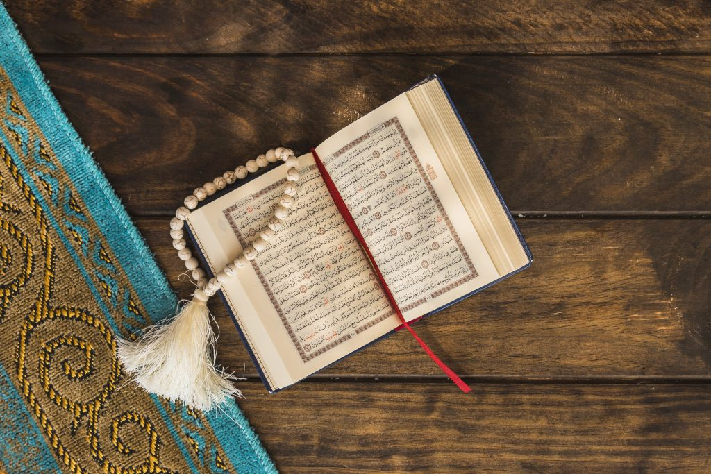 Beads and opened quran near mat