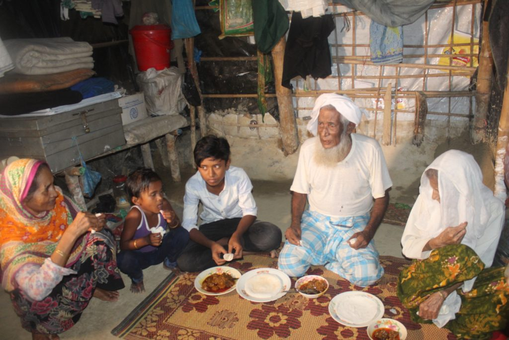 Man sits with his family in a refugee camp in Bangladesh.