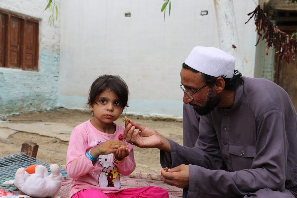Visually impaired father feeds his daughter from food he received in online qurbani Canada.