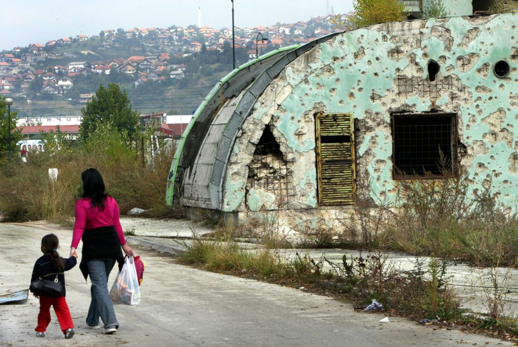 Srebrenica massacre - A woman walks with her daughter against building in Bosnia.