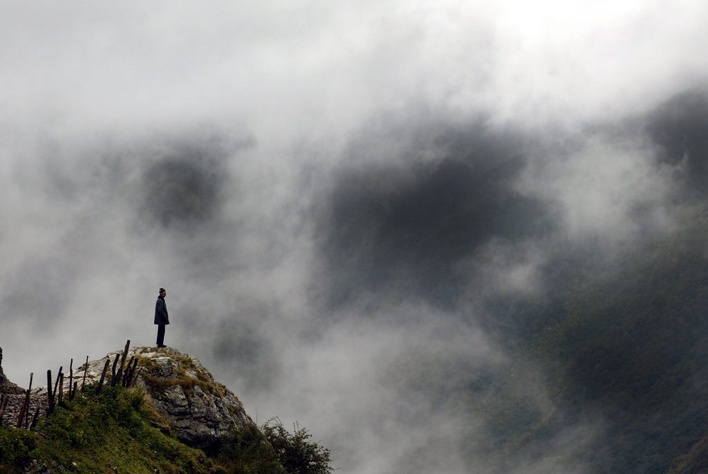 Bosnian man stand atop mountain looking over his country.