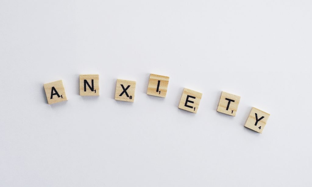 Anxiety spelled out in tile letters on white background