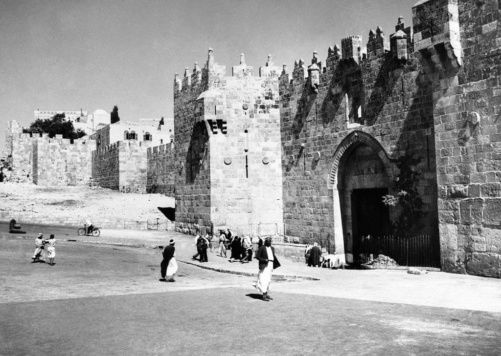 Old photo of Damascus Gate in Palestine as man walks by.