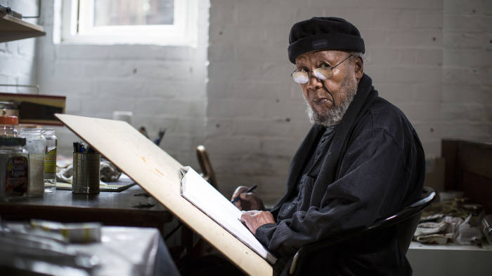 Ibrahim El Salah sits at a desk looking at the camera. His work is a reflection of Islam in Sudan.