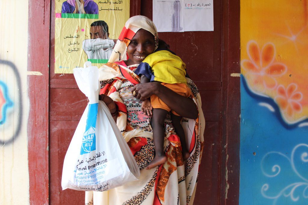 Smiling Sudanese woman holds child while showing relief package from Islamic Relief.