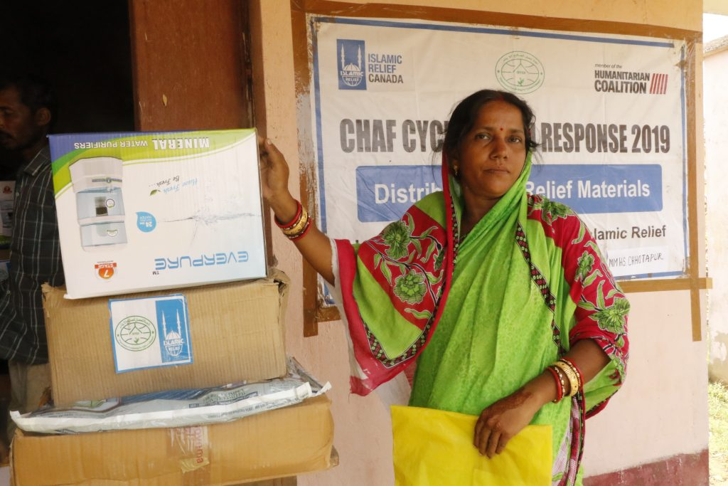 Woman holds her new water purifier received from Humanitarian Coalition