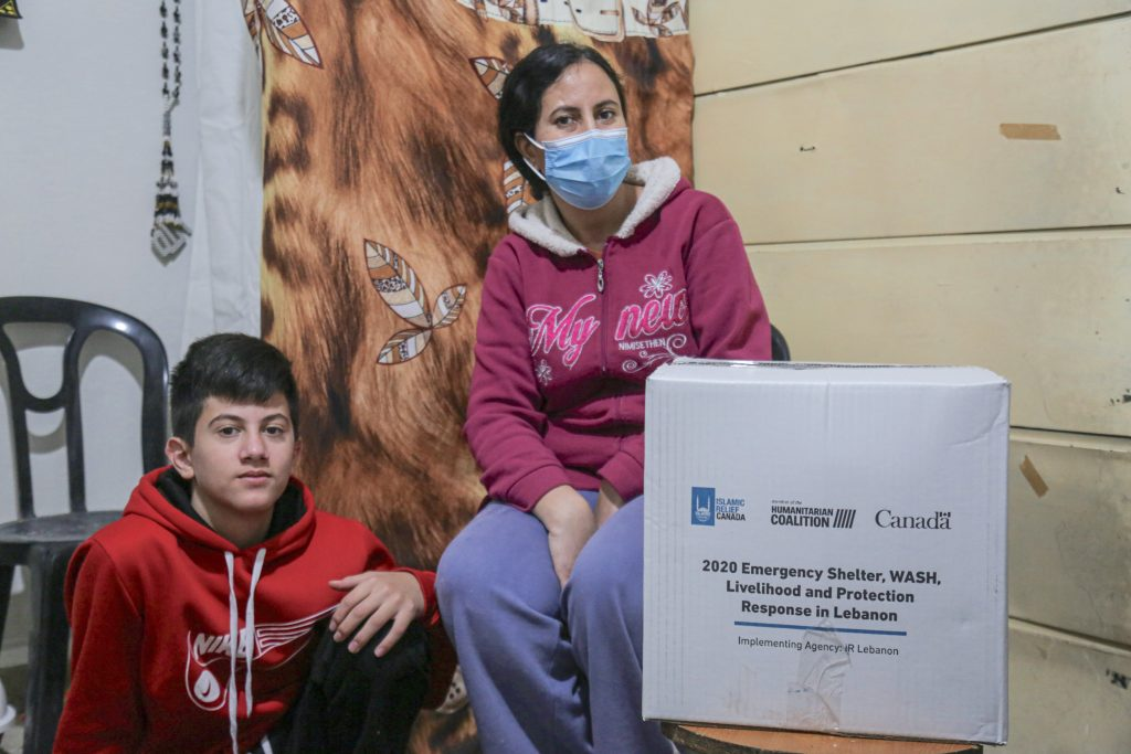 Hanaa with her son in Lebanon receiving hygiene kit from Islamic Relief Canada and Humanitarian Coalition
