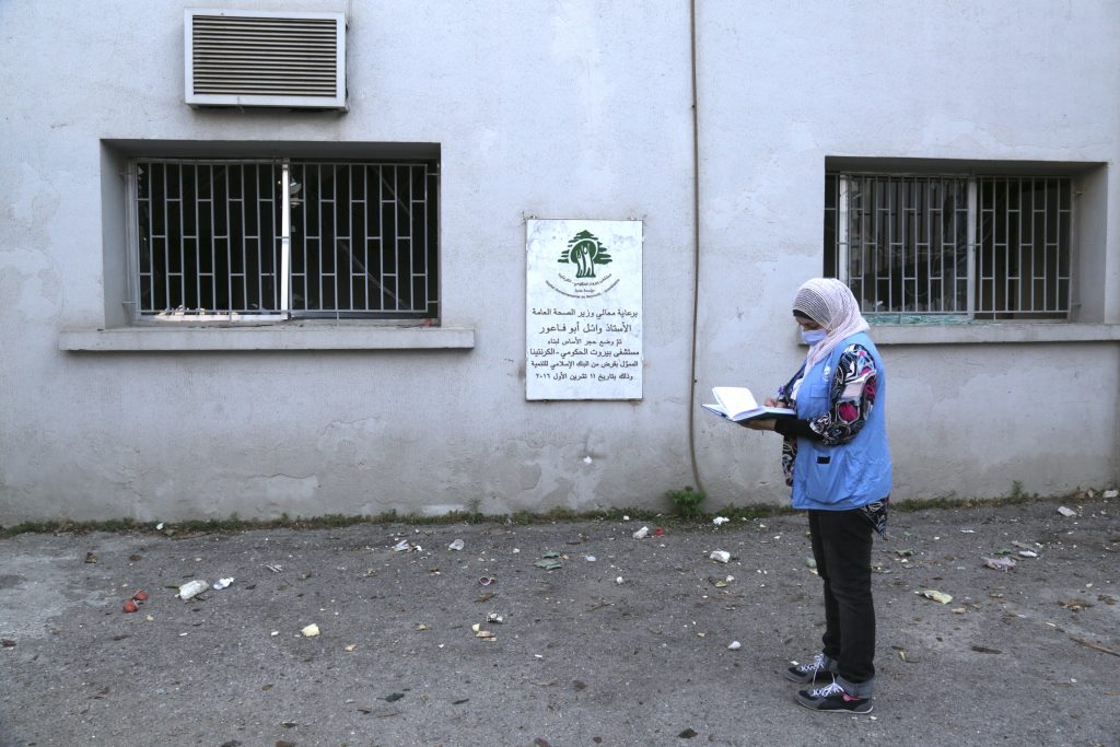 Islamic Relief staff - Woman standing with a clipboard during Lebanon Blast assessment for Humanitarian Coalition.
